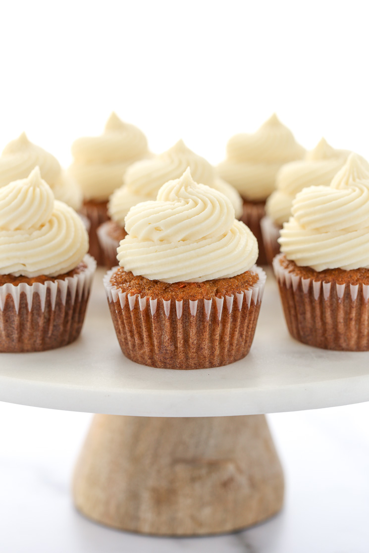 A group of carrot cake cupcakes topped with cream cheese frosting resting on top of a marble cake stand with wooden base.