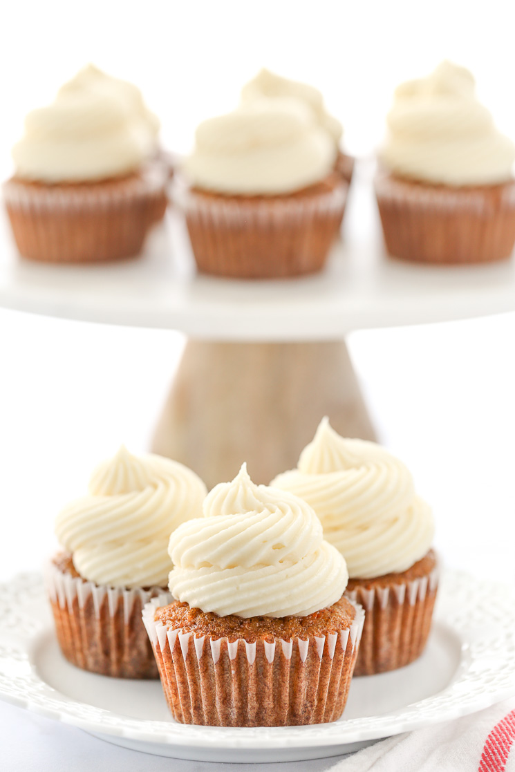 A decorative white plate holding three carrot cake cupcakes topped with cream cheese frosting in front of a marble cake stand.
