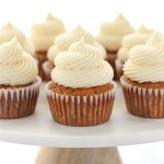 A group of carrot cake cupcakes topped with cream cheese frosting setting on top of a marble cake stand.