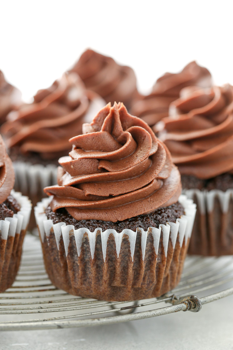 A close up picture of chocolate cupcakes topped with chocolate cream cheese frosting sitting on top of an antique round cooling rack.