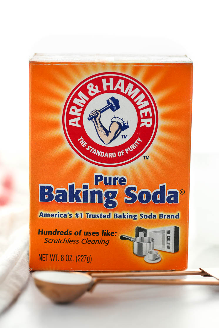 A box of baking soda behind a measuring spoon on top of a marble surface.