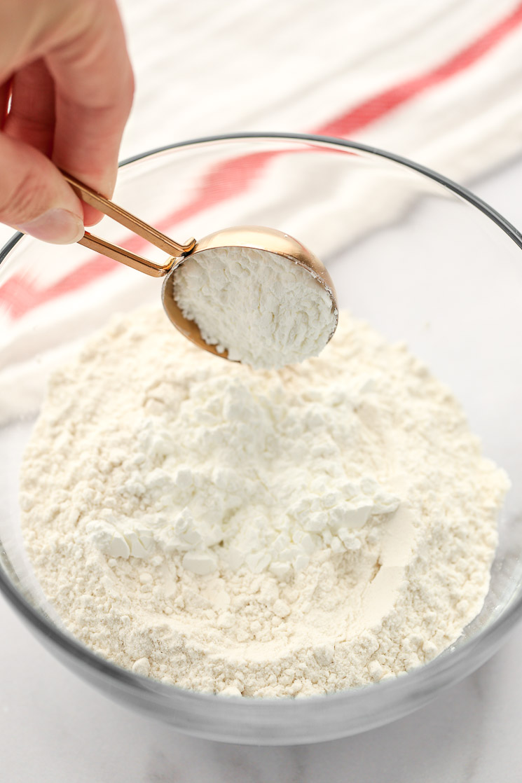 A glass bowl filled with all-purpose flour and two tablespoons of cornstarch.