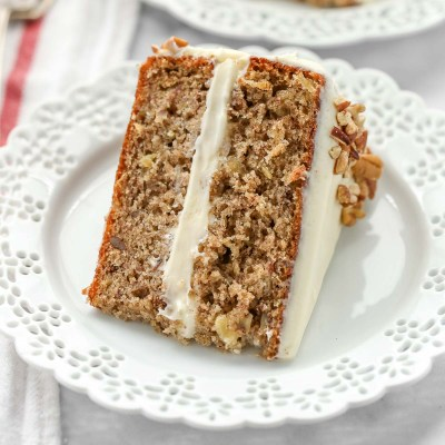 A slice of hummingbird cake on a decorative white plate.