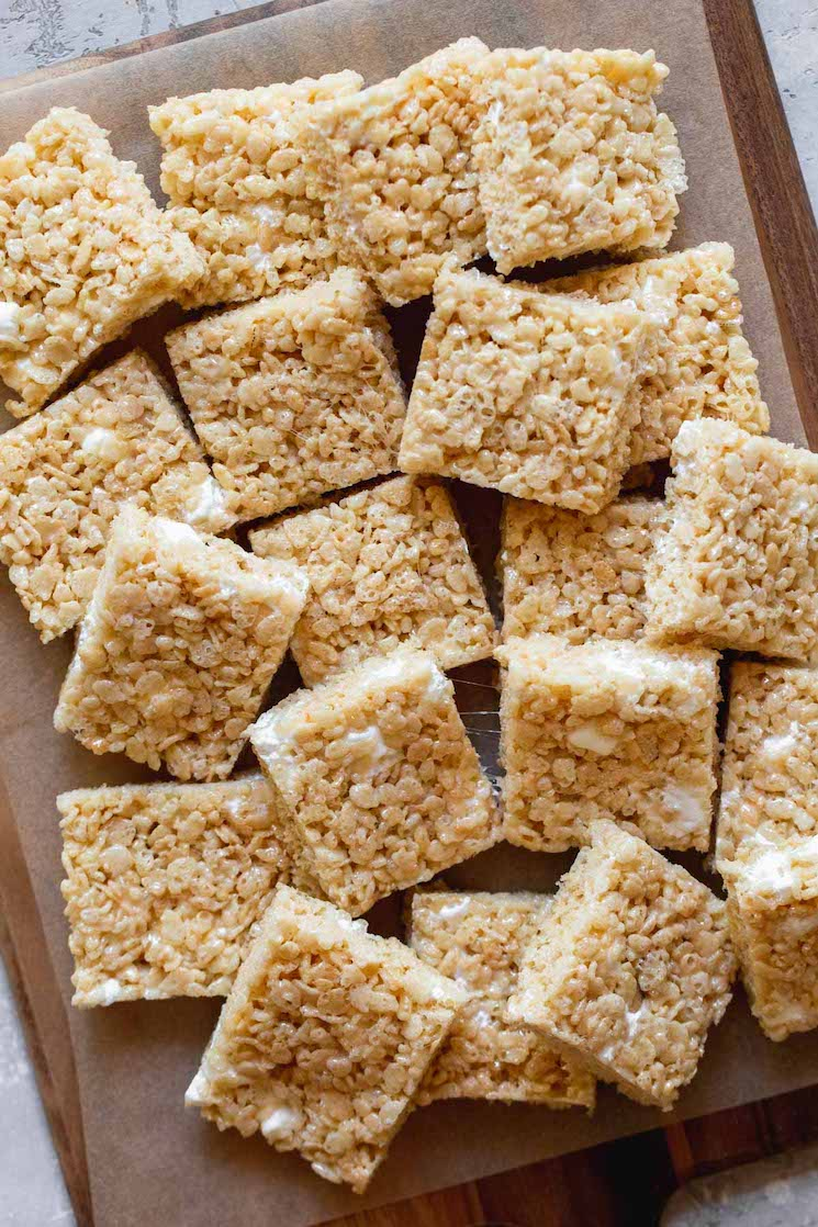 Multiple Rice Krispie treats squares arranged on a wooden tray.