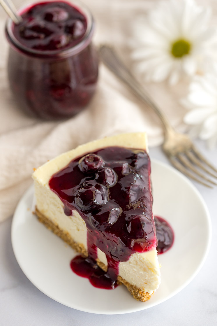 A slice of cheesecake topped with blueberry sauce on a white plate.