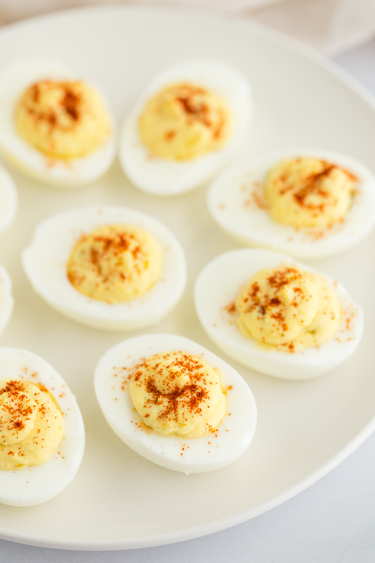 Deviled eggs sitting on top of a white matte plate.