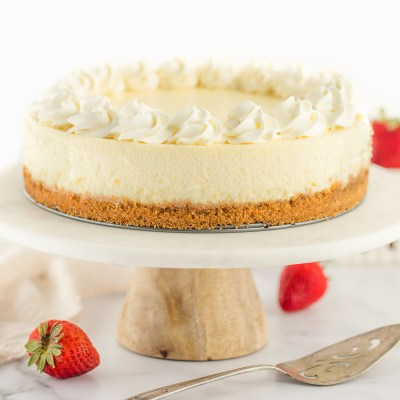 A cheesecake topped with whipped cream sitting on a marble cake stand.