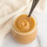 A close-up image of dulce de leche in a small glass jar.
