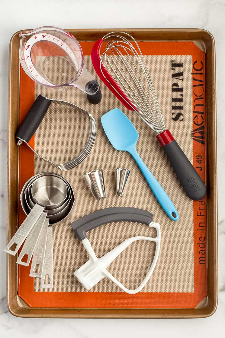 A baking sheet displaying multiple baking tools such as a whisk, measuring cups, and piping tips.