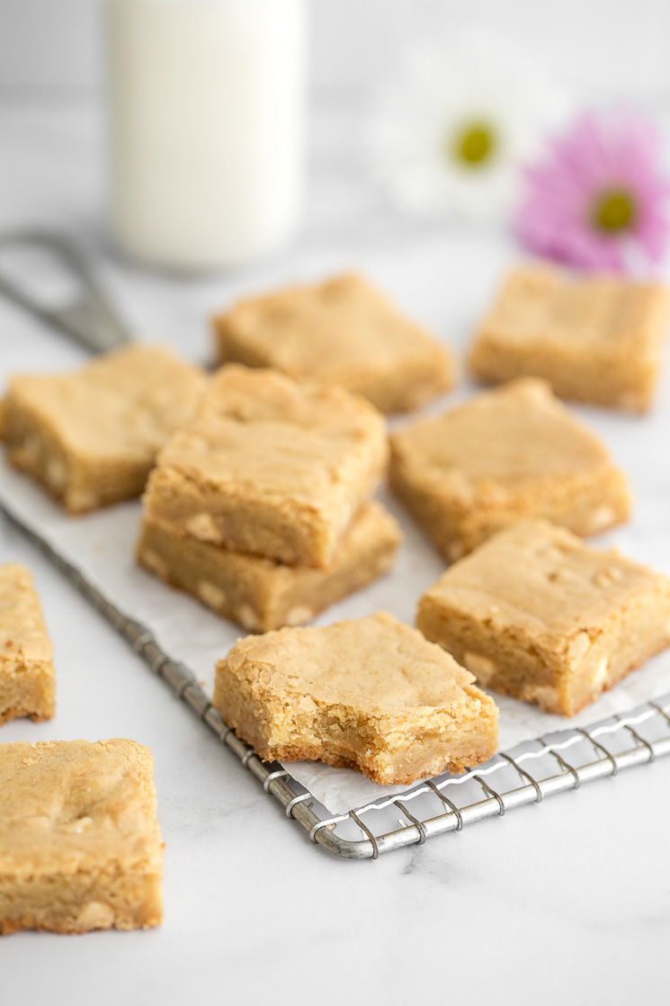Sliced blondies sitting on top of an antique safety grater with more blondies around them.