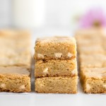 A close-up of a stack of sliced blondies with more blondies around them.