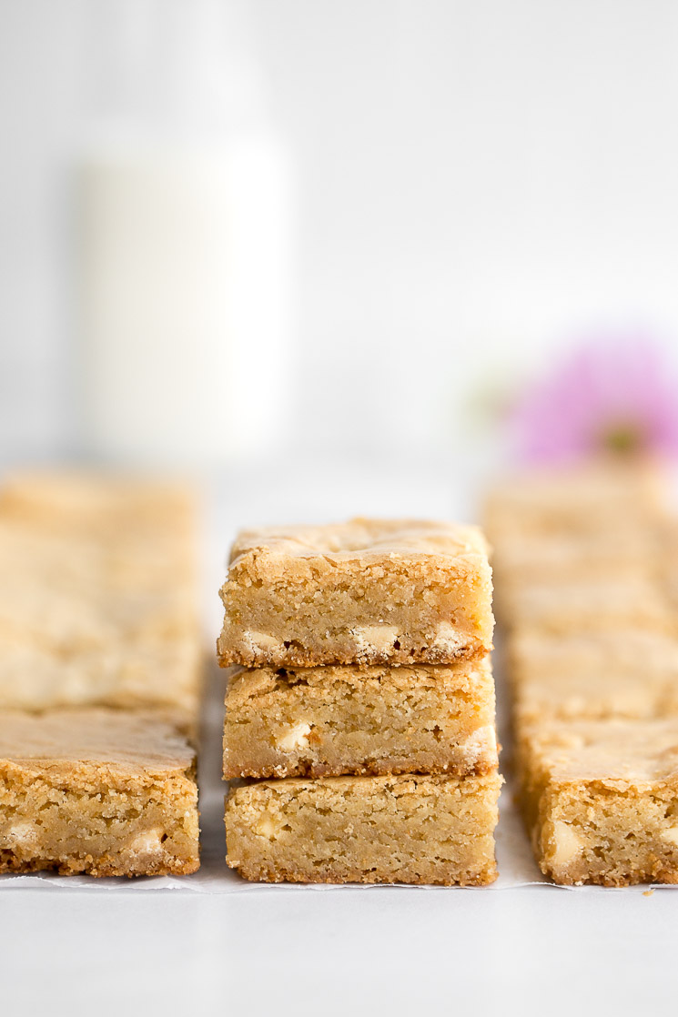 A stack of blondies with more blondies around it and a container of milk in the background.