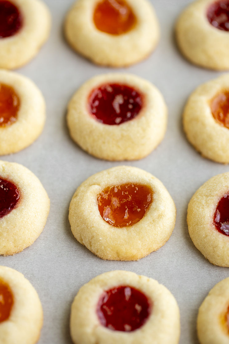Baked thumbprint cookies lined up on a piece of parchment paper.