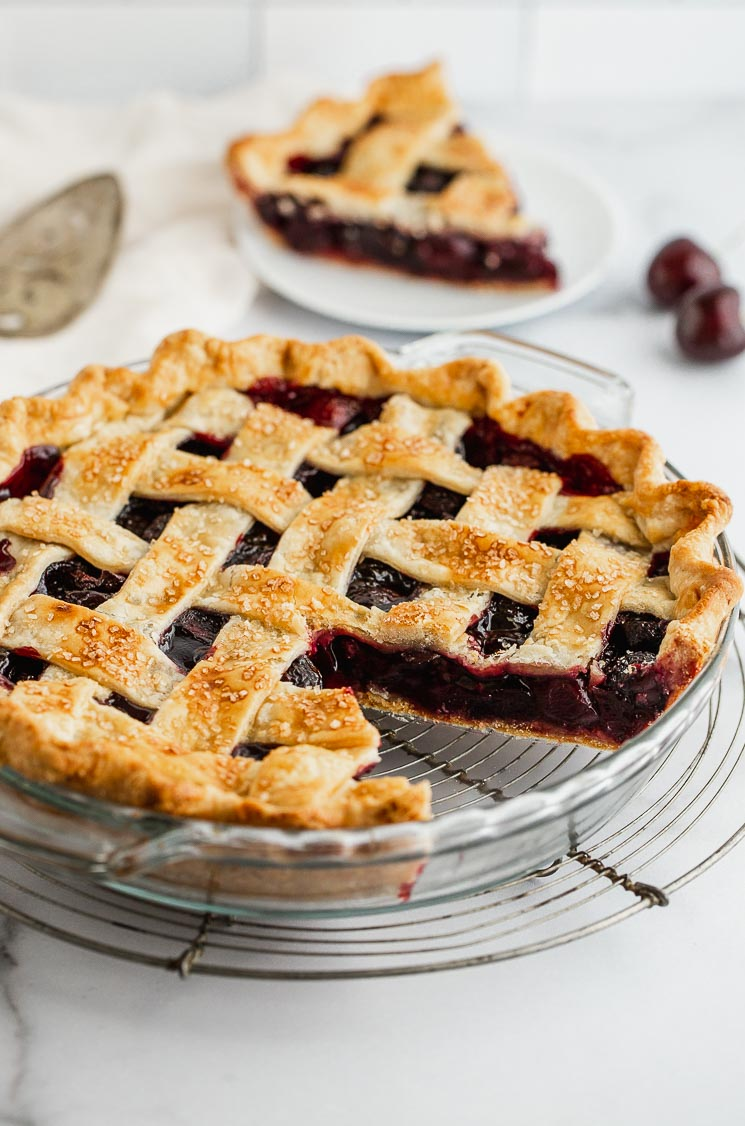 A cherry pie with one slice taken out showing the lattice crust and cherry filling.