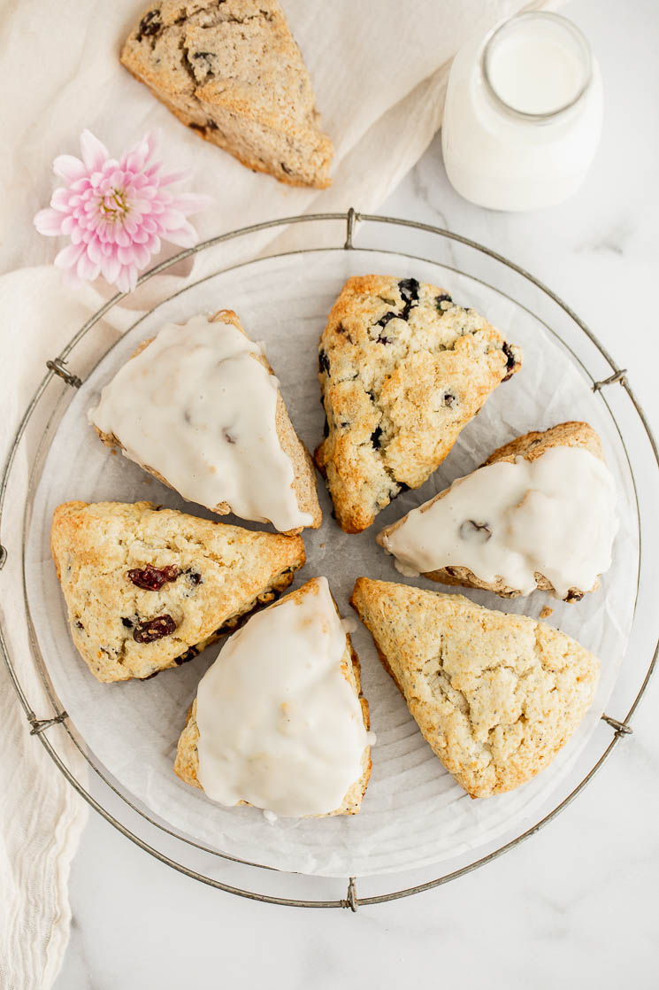 A variety of scones in a circle on a cooling rack with milk and an extra scone in the background.