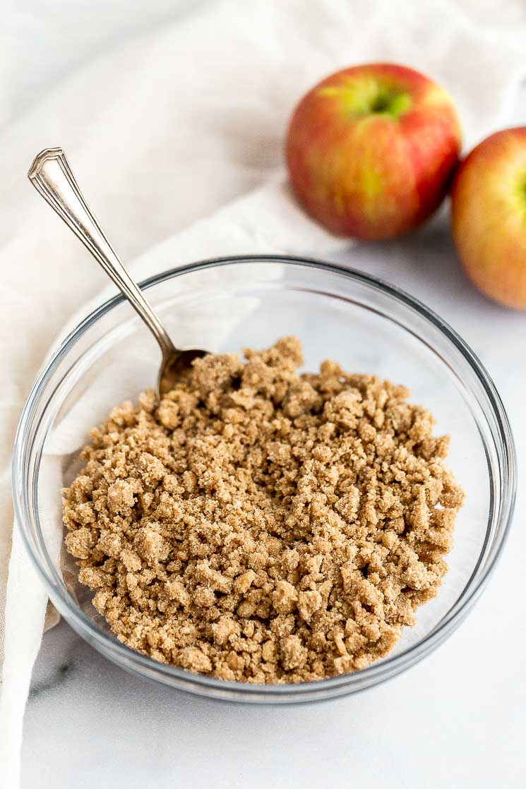 A bowl filled with streusel topping and apples in the background.