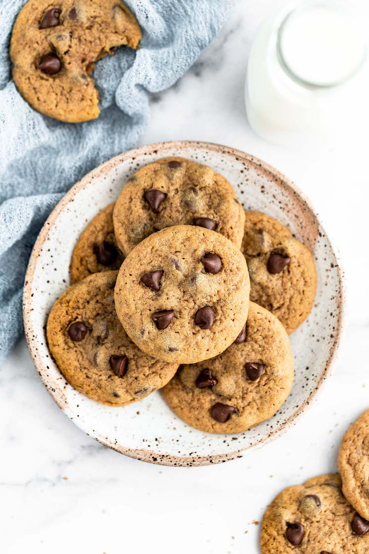 Pumpkin chocolate chip cookies on a speckled plate with milk and more cookies around them.