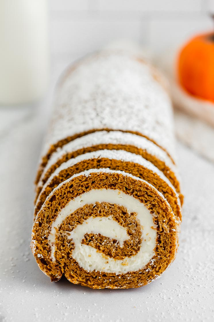 A sliced pumpkin roll with milk and a pumpkin in the background.