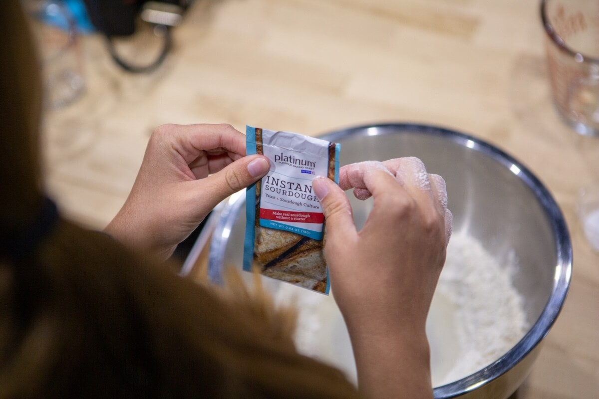 A picture of a person holding a packet of yeast over a bowl of flour.