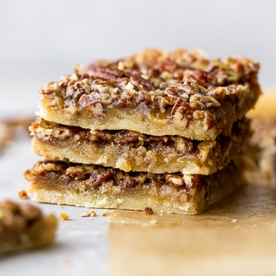 A stack of three pecan pie bars on brown parchment paper.
