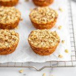 Baked banana oatmeal cups lined up on a cooling rack.