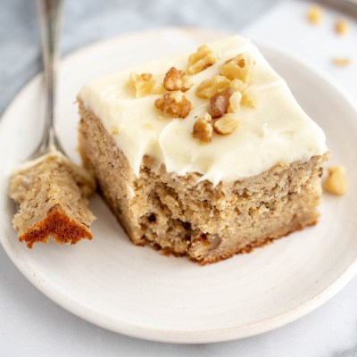 A slice of banana cake with a piece taken out of it.