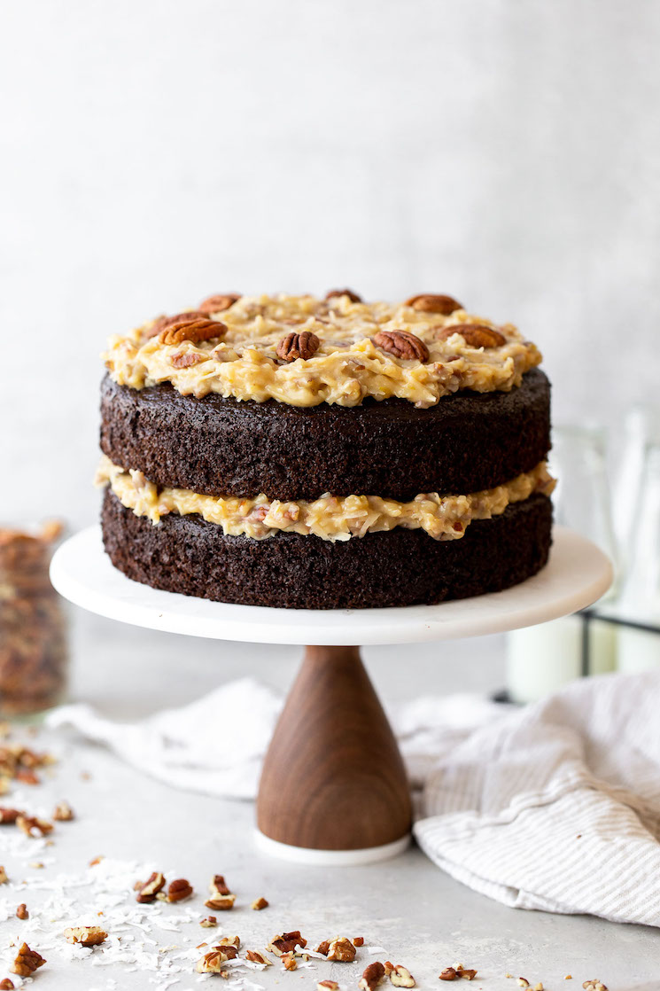 A layered German Chocolate Cake on a marble cake stand with chopped pecans and coconut around it.