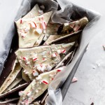 A metal loaf pan with pieces of peppermint bark topped with crushed candy canes.