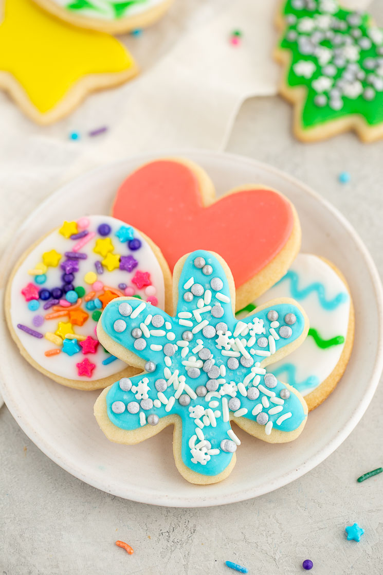 A white plate holding cut-out sugar cookies decorated with easy sugar cookie icing surrounded by more cookies and sprinkles.