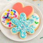 A white plate holding cut-out sugar cookies decorated with easy sugar cookie icing.