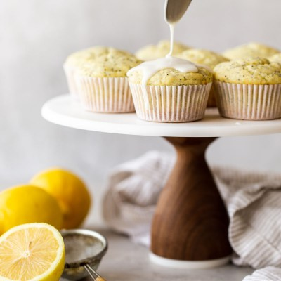 A marble cake stand with lemon poppy seed muffins being topped with a lemon glaze.