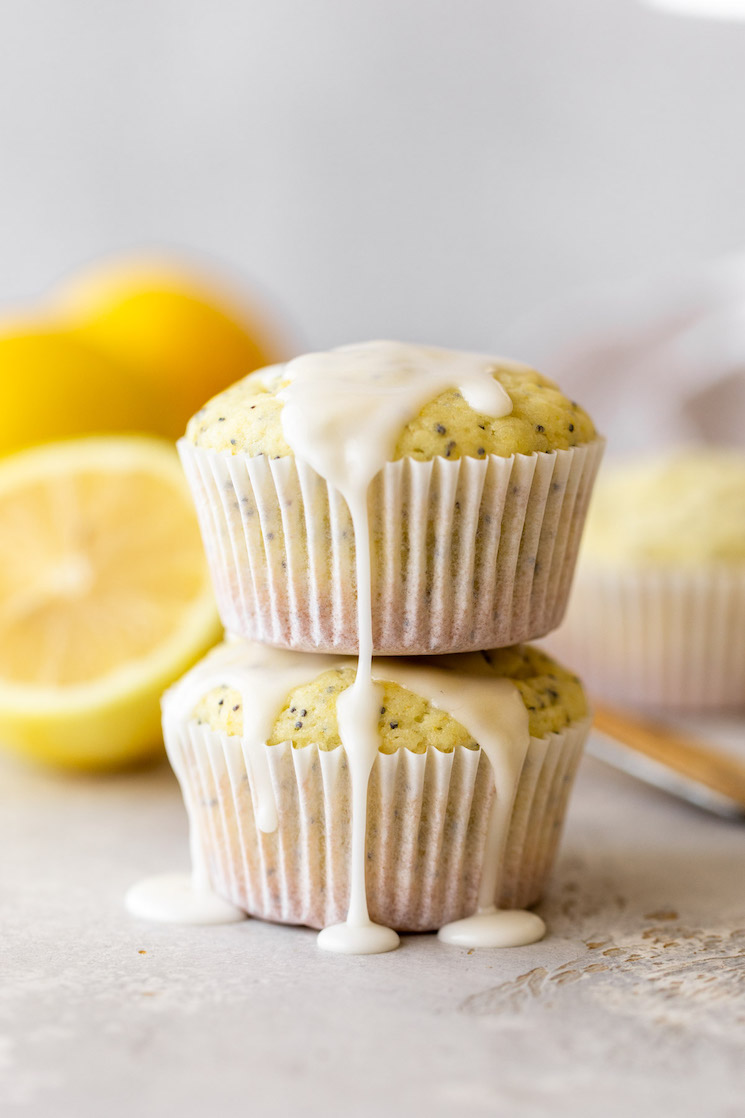 Two muffins stacked with lemon glaze on top and running down the sides.