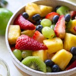 A white bowl filled with fresh fruit salad.