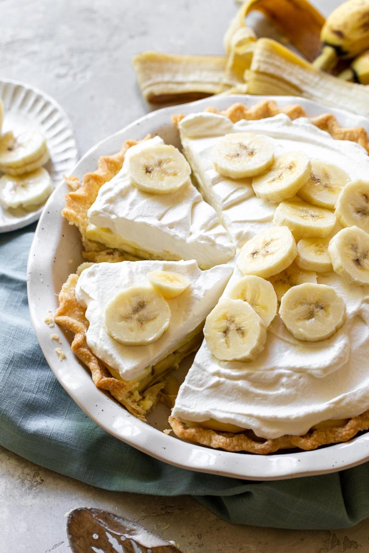 A finished banana cream pie with one piece removed and two more separated to show the layers and texture of the pie.
