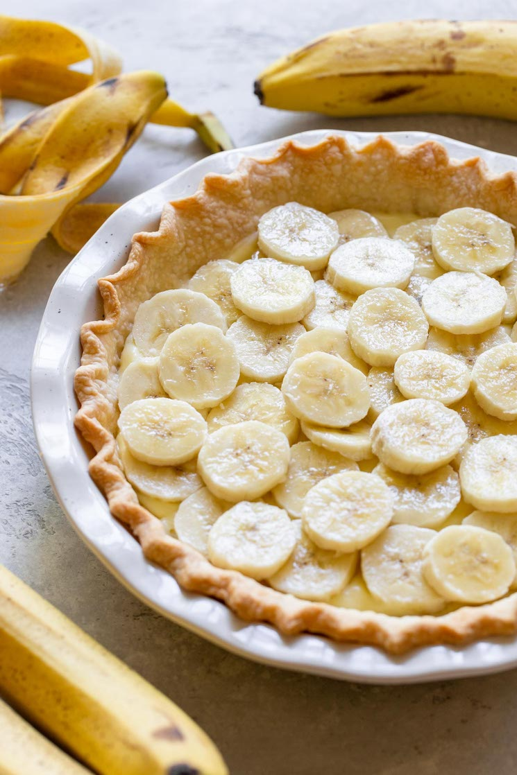 A pie crust filled with a layer of custard filling and sliced bananas.