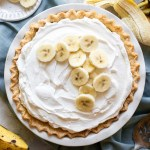 An overhead picture of a finished banana cream pie with extra banana slices on top of the whipped cream.
