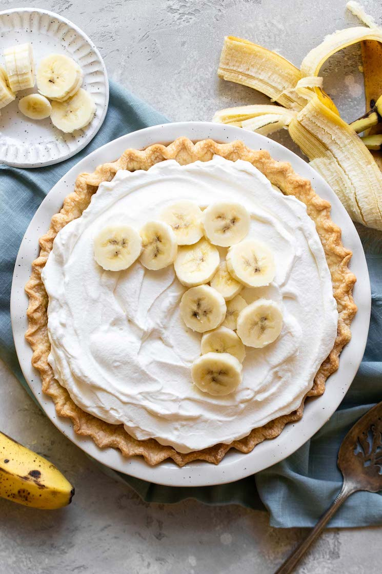 A finished banana cream pie in a white pie plate with banana slices on top with more bananas and a pie server next to it.