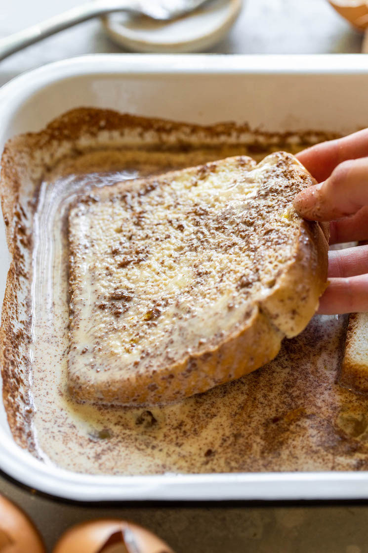 A piece of bread being dipped into the egg mixture showing how it should be covered completely and soaked into the bread.