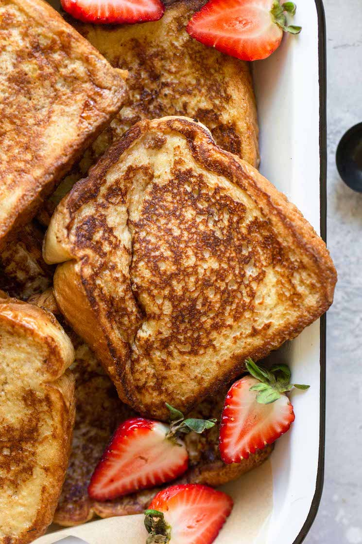 A close up image of French toast in a baking pan topped with halved strawberries.