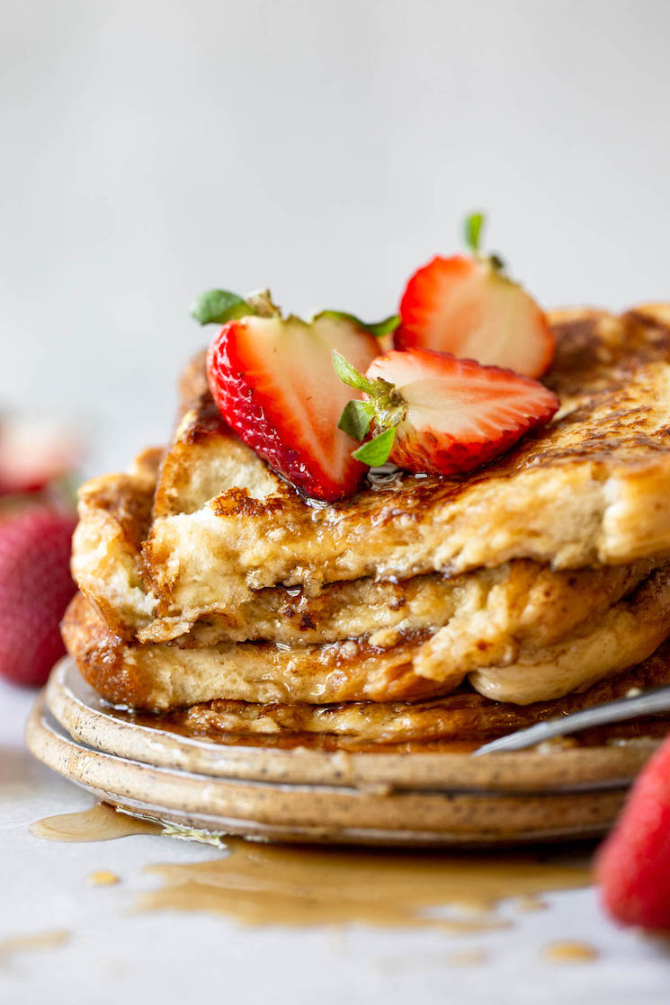 A plate holding French toast stacked up and topped with syrup and halved strawberries.