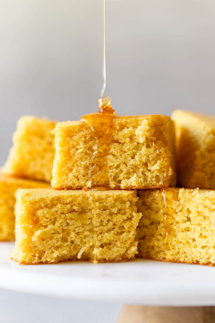 A stack of cornbread on a marble cake stand topped with honey.
