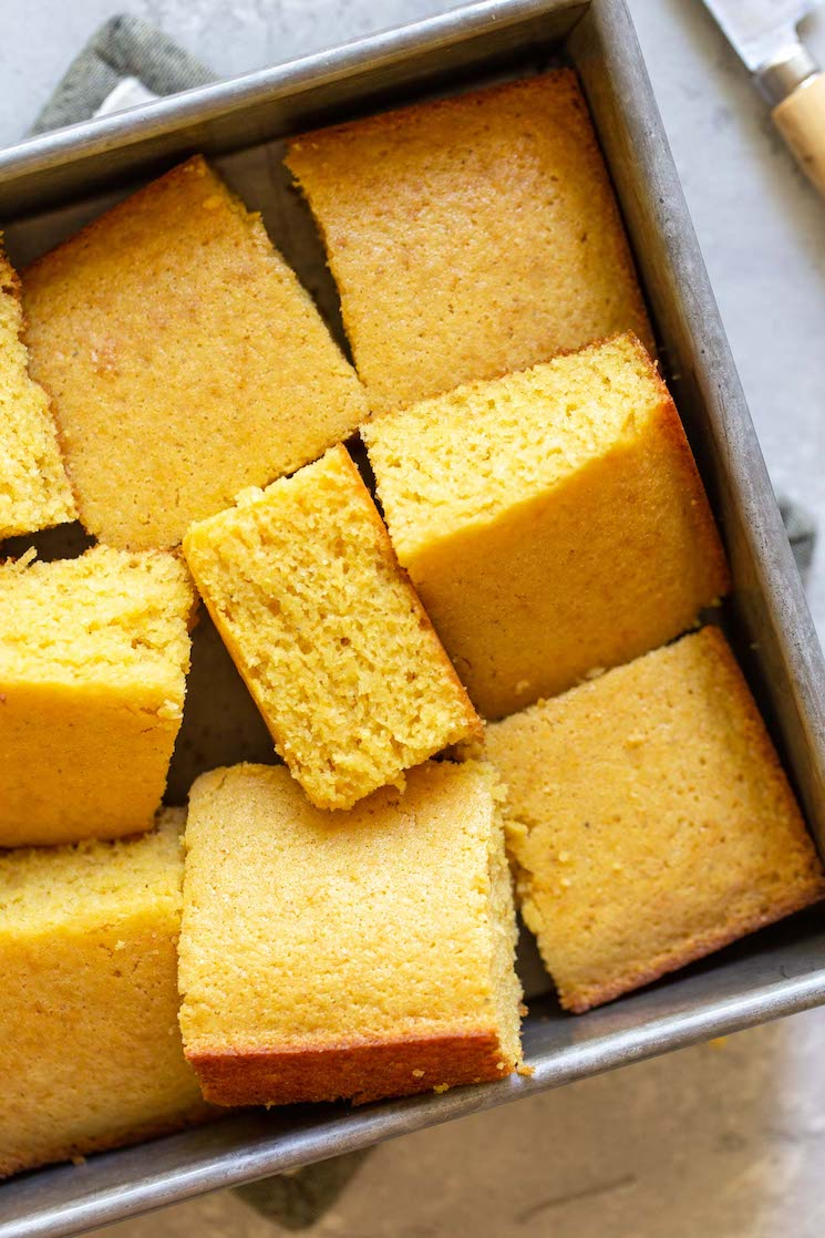 A pan of cornbread pieces cut and laid randomly into a metal baking pan showing different perspectives of each piece.