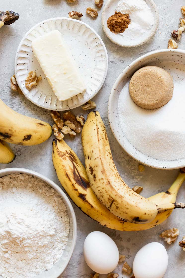 The ingredients needed to make banana bread laying on a gray surface in speckled bowls and plates.