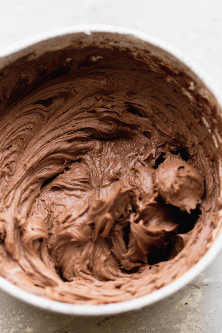 A white mixing bowl filled with chocolate buttercream frosting.