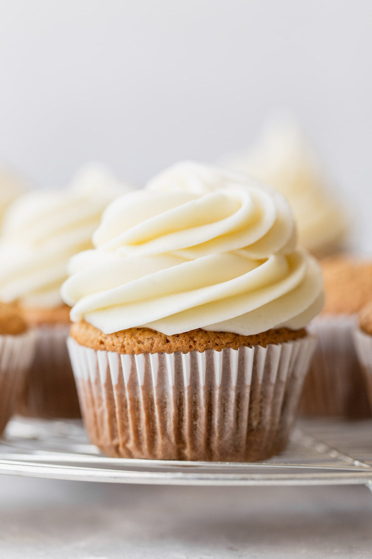 A group of cupcakes resting on a round cooling rack topped with cream cheese frosting.