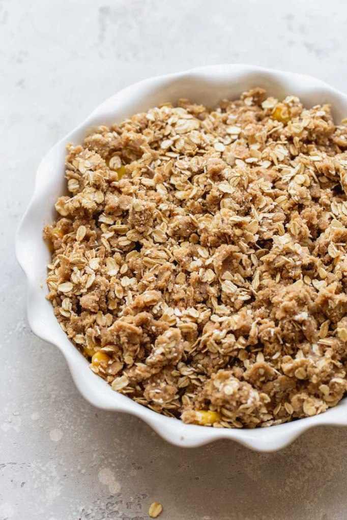 A round white baking dish with sliced peaches topped with the oat topping ready to be baked.