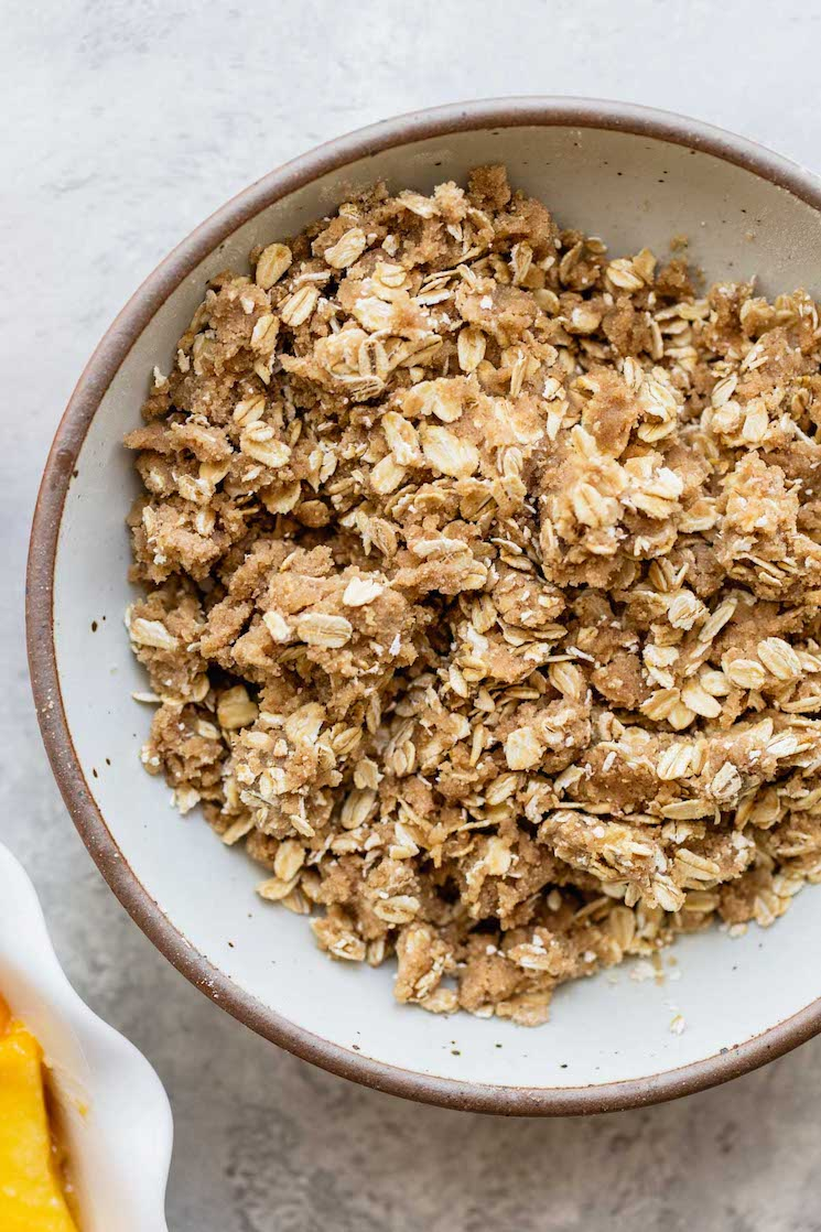 A white bowl filled with brown sugar oat topping.