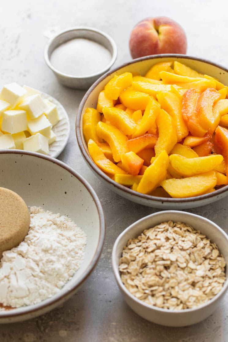 The ingredients needed to make peach crisp in various bowls on a gray surface.
