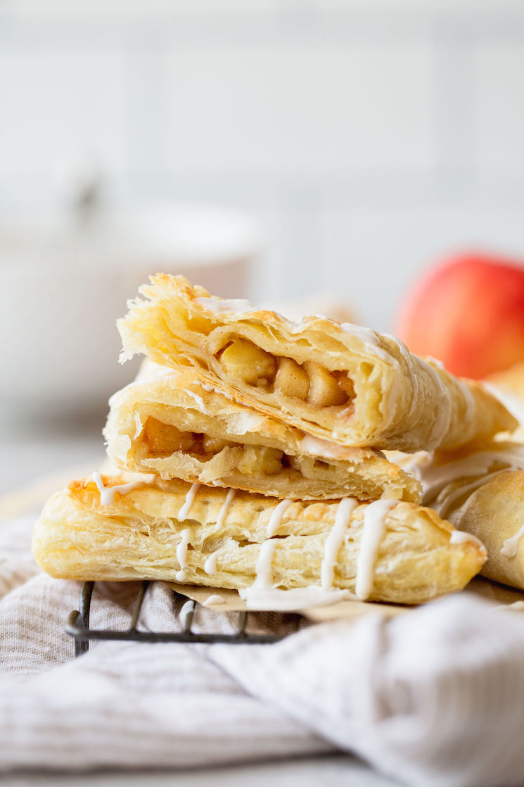 A stack of apple turnovers with one cut in half showing the apple filling.