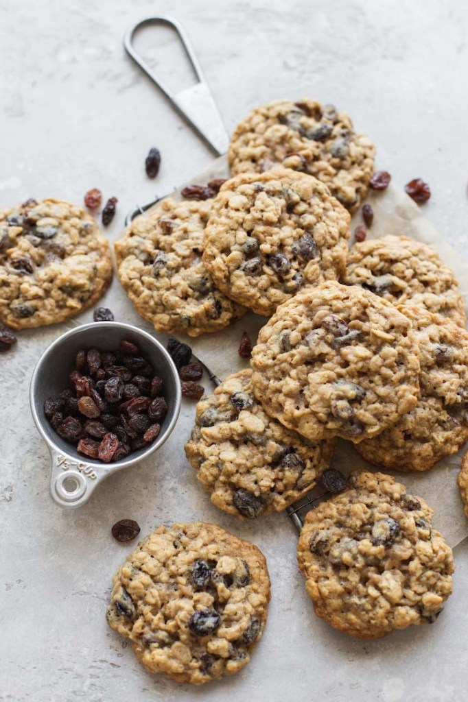 A batch of cookies laid out on top of a small cooling rack with more raisins scattered around them.